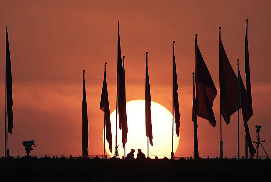 Chinese military personnel watch over Tiananmen Square from a rooftop across from the Great Hall of the People, as the sun rises before the opening session of the National People's Congress in Beijing Thursday, March 5, 2015. (AP Photo/Andy Wong)