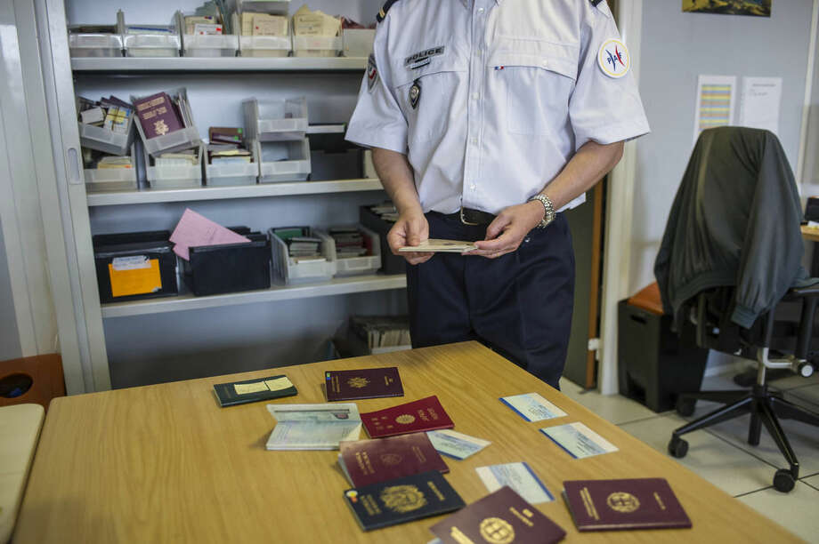 French expert of the French Office of False Documents and Identity Fraud, Laurent Gauthier, shows false passports during an interview with The Associated Press in Paris, Wednesday, June 10, 2015. Police, immigration specialists and hi-tech experts from 16 countries are seeking ways to tackle the growing problem of identity and document fraud that feeds the movement of terrorists across borders, social welfare scams and preys on refugees seeking a safe haven in the West. Your lost or stolen passport may have found a new life in the shady underworld of a crime gang or in the pocket of a terrorist plotting an attack, like the strikes in Paris or the Brussels bombings. (AP Photo/Kamil Zihnioglu, File)