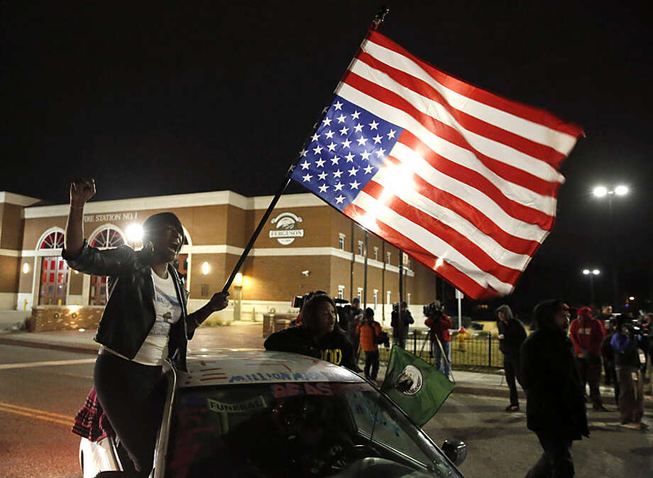 Gina Gowdy joins protesters on the street outside a Ferguson, Mo., fire station, Wednesday, March 4, 2015, in Ferguson. The Justice Department on Wednesday cleared a white former Ferguson police officer in the fatal shooting of an unarmed black 18-year-old, but also issued a scathing report calling for sweeping changes in city law enforcement practices it called discriminatory and unconstitutional. (AP Photo/Charles Rex Arbogast)