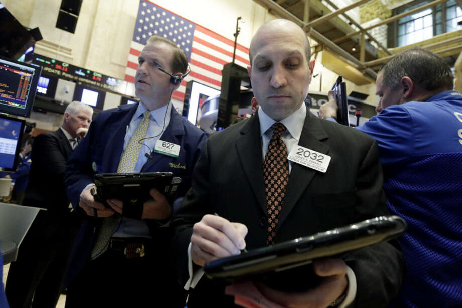 Traders Michael Smyth, left, and James Denaro work on the floor of the New York Stock Exchange, Wednesday, April 6, 2016. Stocks are wobbling in early trading Wednesday. Health care companies are trading higher, energy companies are rising along with the price of oil and telecommunications companies are slipping. (AP Photo/Richard Drew)