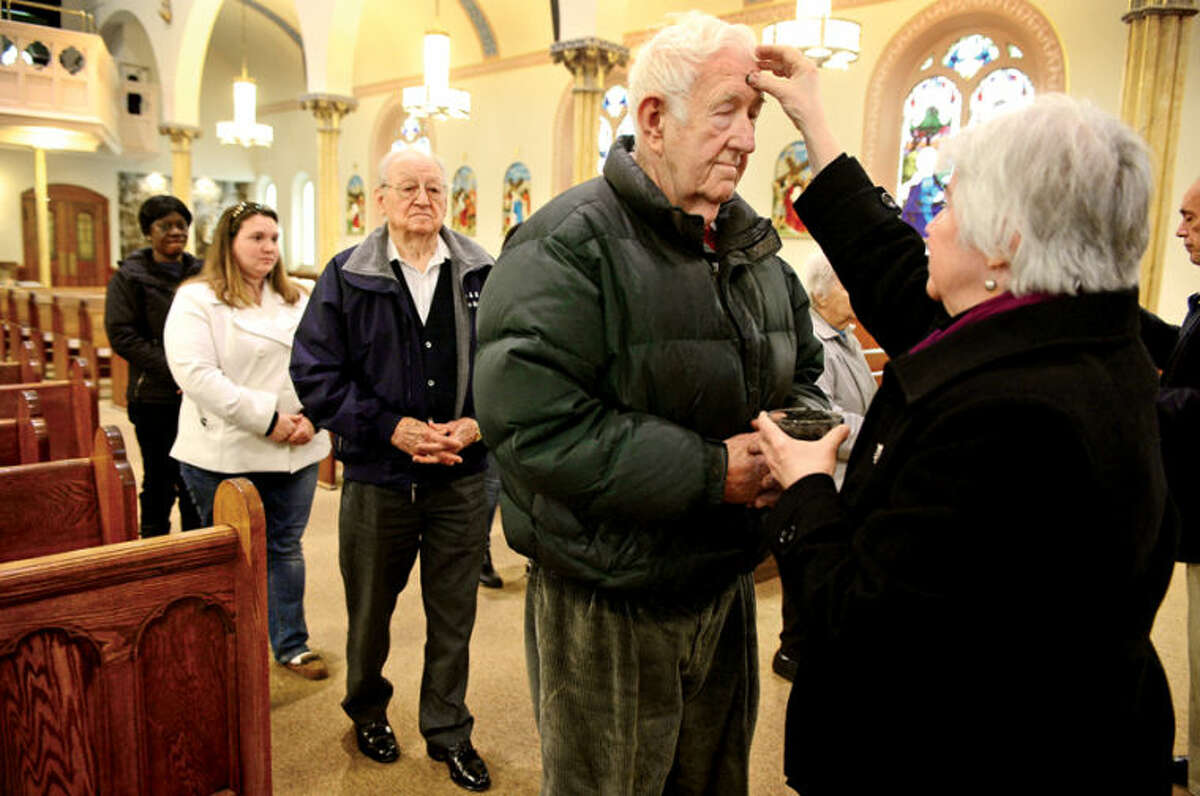 Hour photo / Erik Trautmann Parishioners at St. Ladislaus Church in South Norwalk including John Soltesz receive their ashes in prepartaion for Lent Wednesday.