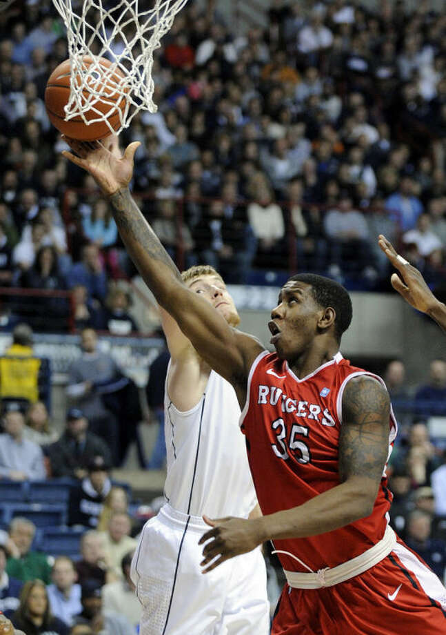 Rutgers' Greg Lewis (35) drives past Connecticut's Niels Giffey (5)during the first half of an NCAA college basketball game in Storrs, Conn., Wednesday, March 5, 2014. (AP Photo/Fred Beckham)