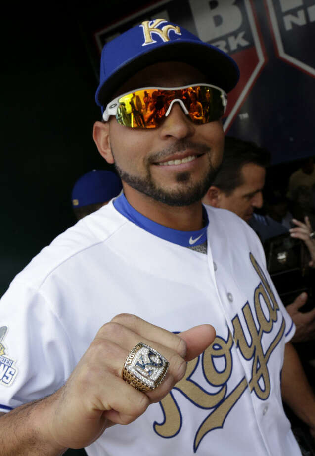 Kansas City Royals' Omar Infante poses for a photograph with his World Series Championship ring before a baseball game against the New York Mets at Kauffman Stadium Monday, April 4, 2016 in Kansas City, Mo. (AP Photo/Colin E. Braley)
