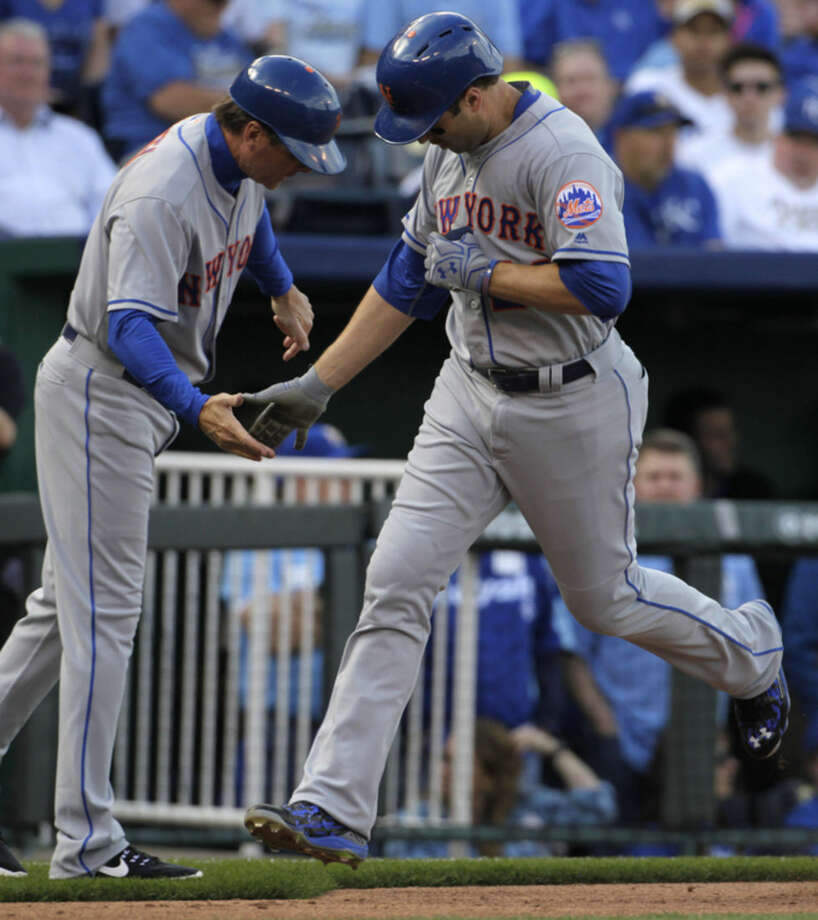 New York Mets second baseman Neil Walker, right, is congratulated by New York Mets third base coach Tim Teufel, left, after his two-run home run during the fourth inning of a baseball game against the Kansas City Royals at Kauffman Stadium in Kansas City, Mo., Tuesday, April 5, 2016. (AP Photo/Colin E. Braley)