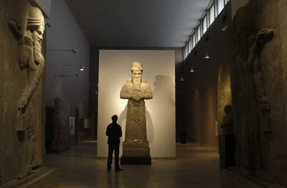 "FILE - In this Nov. 24, 2009 file photo, a journalist looks at an Assyrian statue, center, in front of two Assyrian human-headed winged bulls at Iraq's national museum, in Baghdad. Islamic State militants ""bulldozed"" the renowned archaeological site of the ancient city of Nimrud in northern Iraq on Thursday, March 5, 2015 using heavy military vehicles, the government said. Nimrud was the second capital of Assyria, an ancient kingdom that began in about 900 B.C., partially in present-day Iraq, and became a great regional power. The city, which was destroyed in 612 B.C., is located on the Tigris River just south of Iraq's second largest city, Mosul, which was captured by the Islamic State group in June(AP Photo/Petros Giannakouris, File)"
