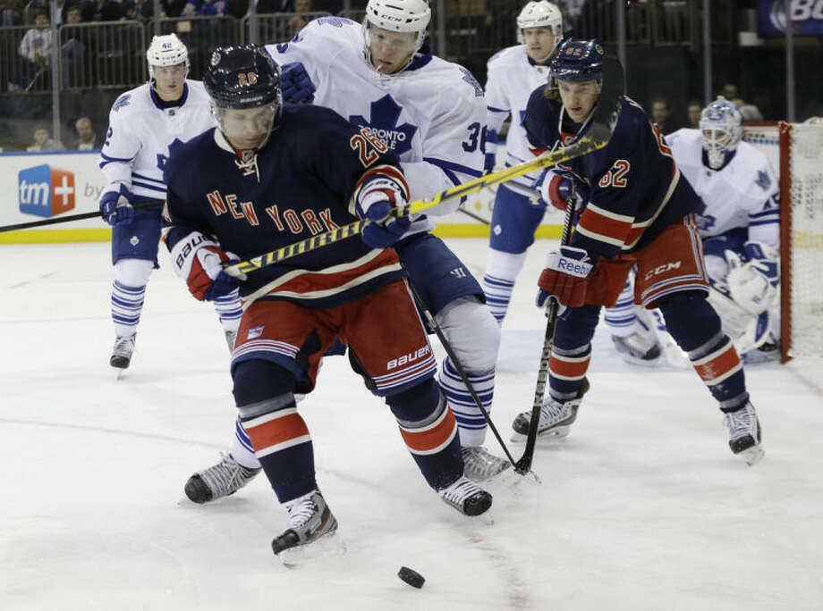 New York Rangers' Martin St. Louis (26) fights for control of the puck with Toronto Maple Leafs' Carl Gunnarsson during the second period of an NHL hockey game Wednesday, March 5, 2014, in New York. (AP Photo/Frank Franklin II)
