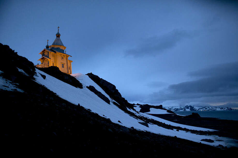 """In this Feb. 1, 2015 photo, the Holy Trinity Church located on top of a rocky hill is illuminated on King George Island, Antarctica. The clapboard church was first built in Russia, then disassembled and shipped log-by-log, """"like Lego blocks,"""" to Antarctica, said Alejo Contreras, a Chilean Antarctic explorer who witnessed the construction and consecration in 2004. (AP Photo/Natacha Pisarenko)"""