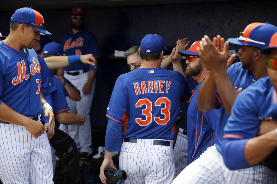 New York Mets starting pitcher Matt Harvey is congratulated by teammates after working the first inning of an exhibition spring training baseball game against the Detroit Tigers Friday, March 6, 2015, in Port St. Lucie, Fla. The game was the first for Harvey in 18 months after it was discovered he had a tear in an elbow ligament in 2013 resulting in the need for surgery. (AP Photo/Jeff Roberson)