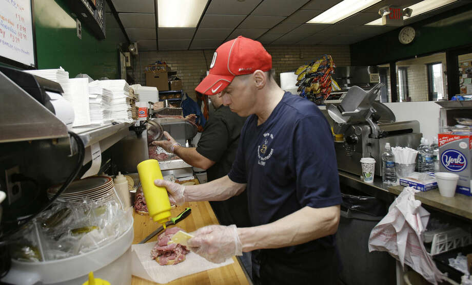 In this Jan. 23, 2015 photo, Mark Childers puts a topping on a corned beef sandwich at the Superior Restaurant in Cleveland. A private survey says growth picked up last month at U.S. services companies. The Institute for Supply Management's services index rebounded to 54.5 in March 2016 from a two-year low 53.4 in February. (AP Photo/Tony Dejak)