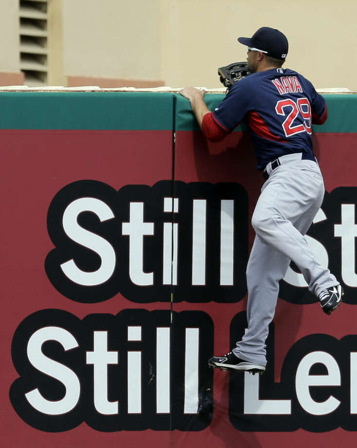 Boston Red Sox left fielder Daniel Nava climbs the outfield wall, watching a two-run home run by St. Louis Cardinals' Xavier Scruggs during the second inning of an exhibition baseball game Wednesday, March 5, 2014, in Jupiter, Fla. (AP Photo/Jeff Roberson)