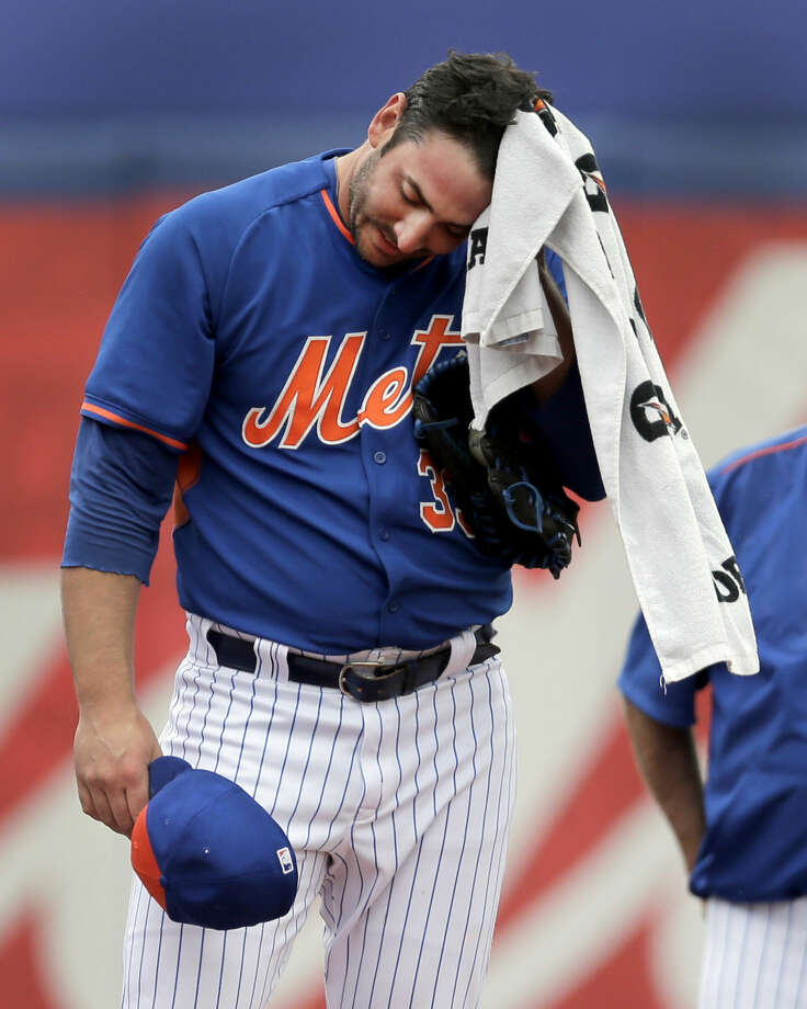 New York Mets pitcher Matt Harvey towels off while warming up before starting an exhibition spring training baseball game against the Detroit Tigers Friday, March 6, 2015, in Port St. Lucie, Fla. The game was the first for Harvey in 18 months after it was discovered he had a tear in an elbow ligament in 2013 resulting in the need for surgery. (AP Photo/Jeff Roberson)