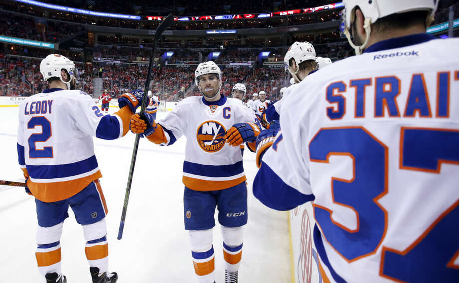 New York Islanders center John Tavares, center, celebrates his goal with defenseman Nick Leddy (2) and defenseman Brian Strait (37) after his goal in the second period of an NHL hockey game against the Washington Capitals, Tuesday, April 5, 2016, in Washington. (AP Photo/Alex Brandon)