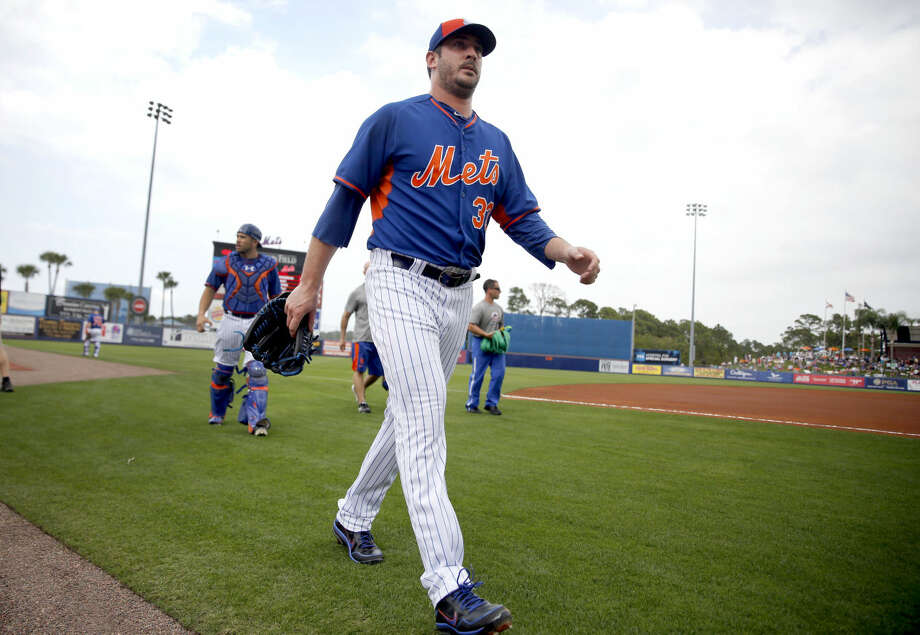 New York Mets pitcher Matt Harvey walks to the dugout after warming to start an exhibition spring training baseball game against the Detroit Tigers Friday, March 6, 2015, in Port St. Lucie, Fla. The game was the first for Harvey in 18 months after it was discovered he had a tear in an elbow ligament in 2013 resulting in the need for surgery. (AP Photo/Jeff Roberson)