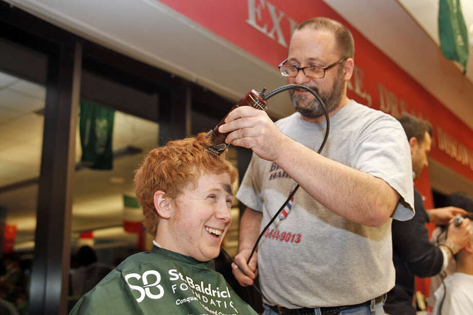 "Colin DeFelice gets his head shaved by Jerry Ventrella during the St. Baldrick's Foundation's ""Shaving the Way to Conquer Kid's Cancer"" event at Wilton High School Wednesday evening."