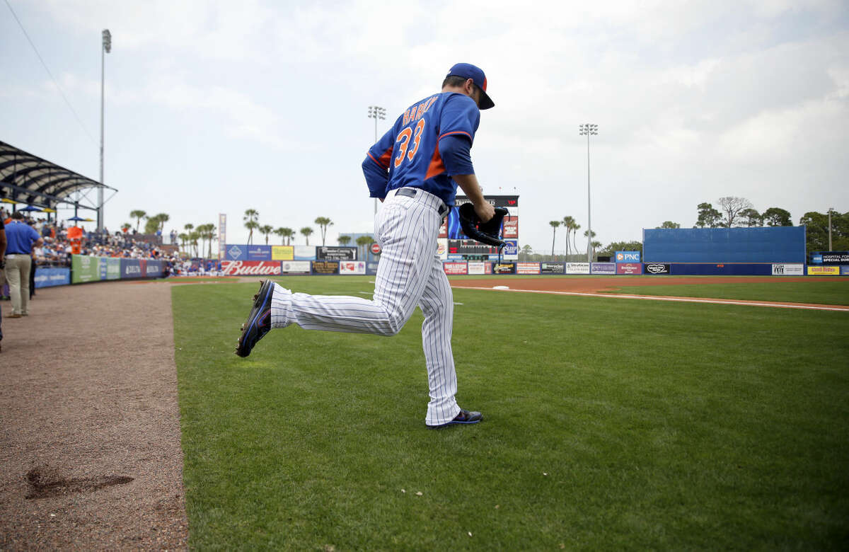 New York Mets pitcher Matt Harvey heads out to the mound to start an exhibition spring training baseball game against the Detroit Tigers Friday, March 6, 2015, in Port St. Lucie, Fla. The game was the first for Harvey in 18 months after it was discovered he had a tear in an elbow ligament in 2013 resulting in the need for surgery. (AP Photo/Jeff Roberson)