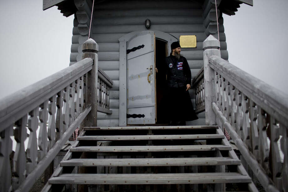 In this Feb. 1, 2015 photo, 38-year-old Russian Orthodox priest Sophrony Kirilov walks out from the Holy Trinity Church, located on top of a rocky hill on King George Island, Antarctica. Kirilov, 38, helps with carpentry and other manual jobs on the weekdays at Russia's Bellinghausen base on the island, and officiates Mass at the world's southernmost Eastern Orthodox church on the weekends. (AP Photo/Natacha Pisarenko)