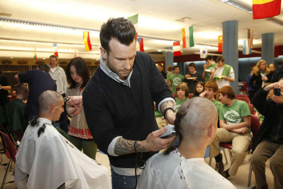 """Price Fidurelli-Reid gets his head shaved by Benjamin Lagasse during the St. Baldrick's Foundation's """"Shaving the Way to Conquer Kid's Cancer"""" event at Wilton High School Wednesday evening."""