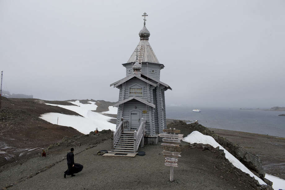 In this Feb. 1, 2015 photo, Russian Orthodox priest Sophrony Kirilov, 38, walks to the Holy Trinity Church, precariously perched on a rocky hill on King George Island, Antarctica. Russian priests here rotate in for yearlong stints, primarily to celebrate Mass for the workers on the Russian Bellinghausen base, which number between 15 and 30 people at a time. (AP Photo/Natacha Pisarenko)