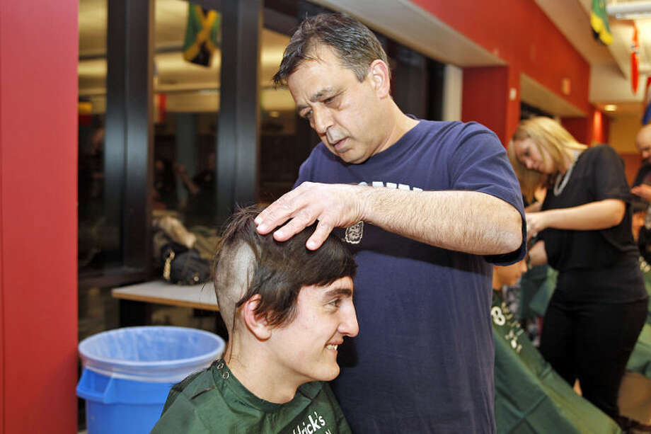 """Jack House gets his head shaved by Guy Monteleone during the St. Baldrick's Foundation's """"Shaving the Way to Conquer Kid's Cancer"""" event at Wilton High School Wednesday evening."""