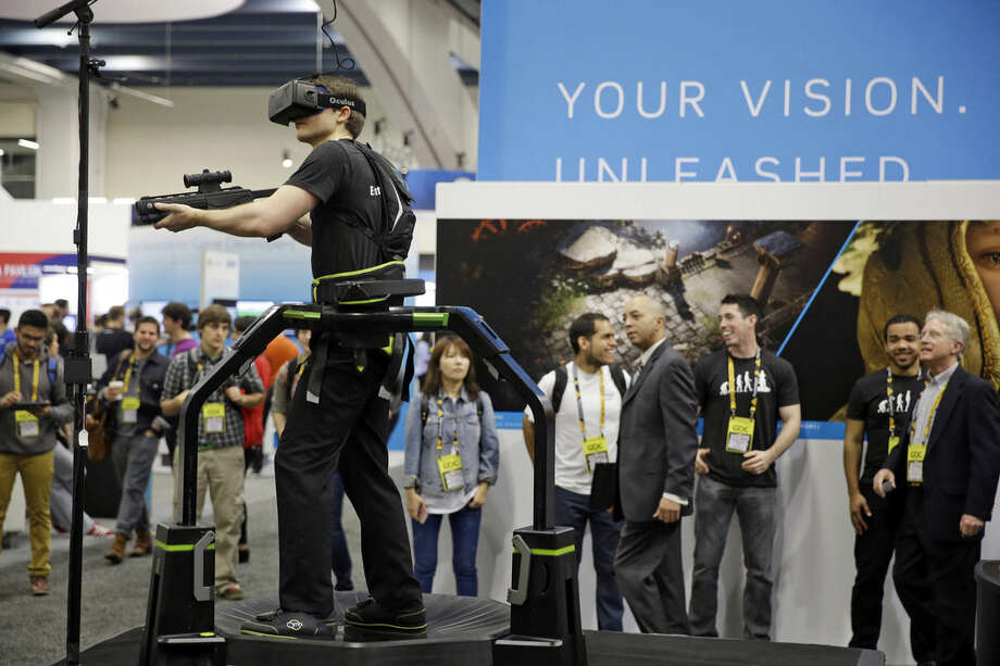 Ben Drakes walks and runs on a Virtuix Omnidirectional gaming treadmill at the Game Developers Conference, Wednesday, March 4, 2015, in San Francisco. (AP Photo/Eric Risberg)
