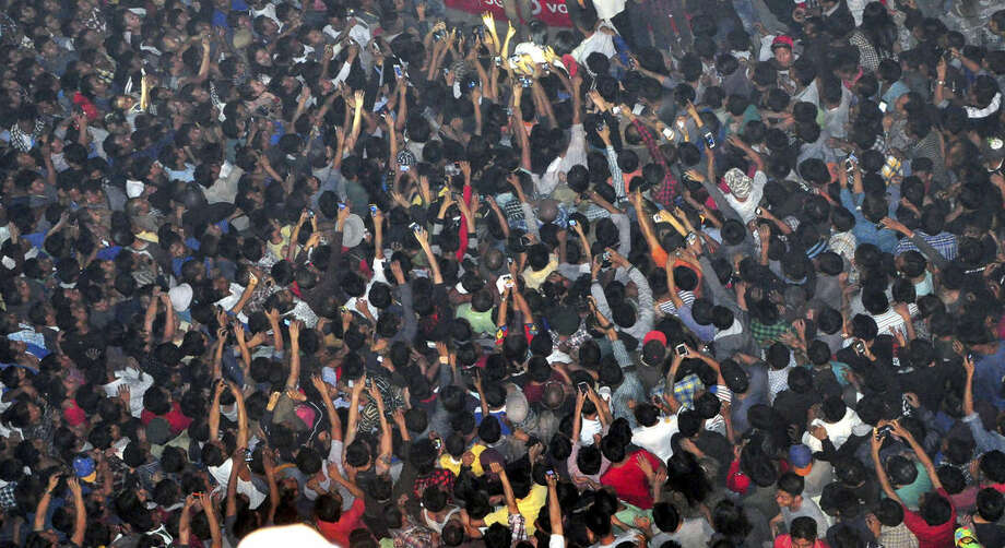 In this Thursday, March 5, 2015 photo, members of a mob raise their hands to take photos of a man, top center, accused of rape after he was lynched and hung in the city landmark Clock Tower in Dimapur, in the northeastern Indian state of Nagaland. Several thousand people overpowered security at Dimapur Central Prison in Nagaland on Thursday, and seized the rape suspect, whom they also accused of being an illegal migrant from Bangladesh. They pelted him with stones and beat him to death, said police Constable Sunep Aier. (AP Photo/Imojen I Jamir)