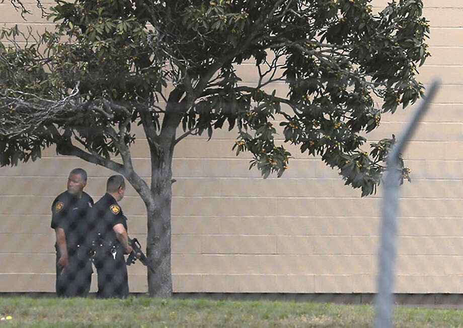 Two Bexar County Sheriff's Deputies stand outside a building near the scene of a shooting at Joint Base San Antonio-Lackland, Friday, April 8, 2016, in San Antonio. (John Davenport/The San Antonio Express-News via AP) RUMBO DE SAN ANTONIO OUT; NO SALES; MANDATORY CREDIT