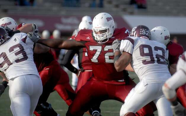 Like a rock in a stream,  former Stamford High School standout lineman Vladimir Ducasse (#72, in red)  is the immovable object in the offensive line for the #7 ranked University of Massachusetts Minutemen as the team's starting left tackle. Photo: File Photo\Paul Desmarais / Stamford Advocate File Photo