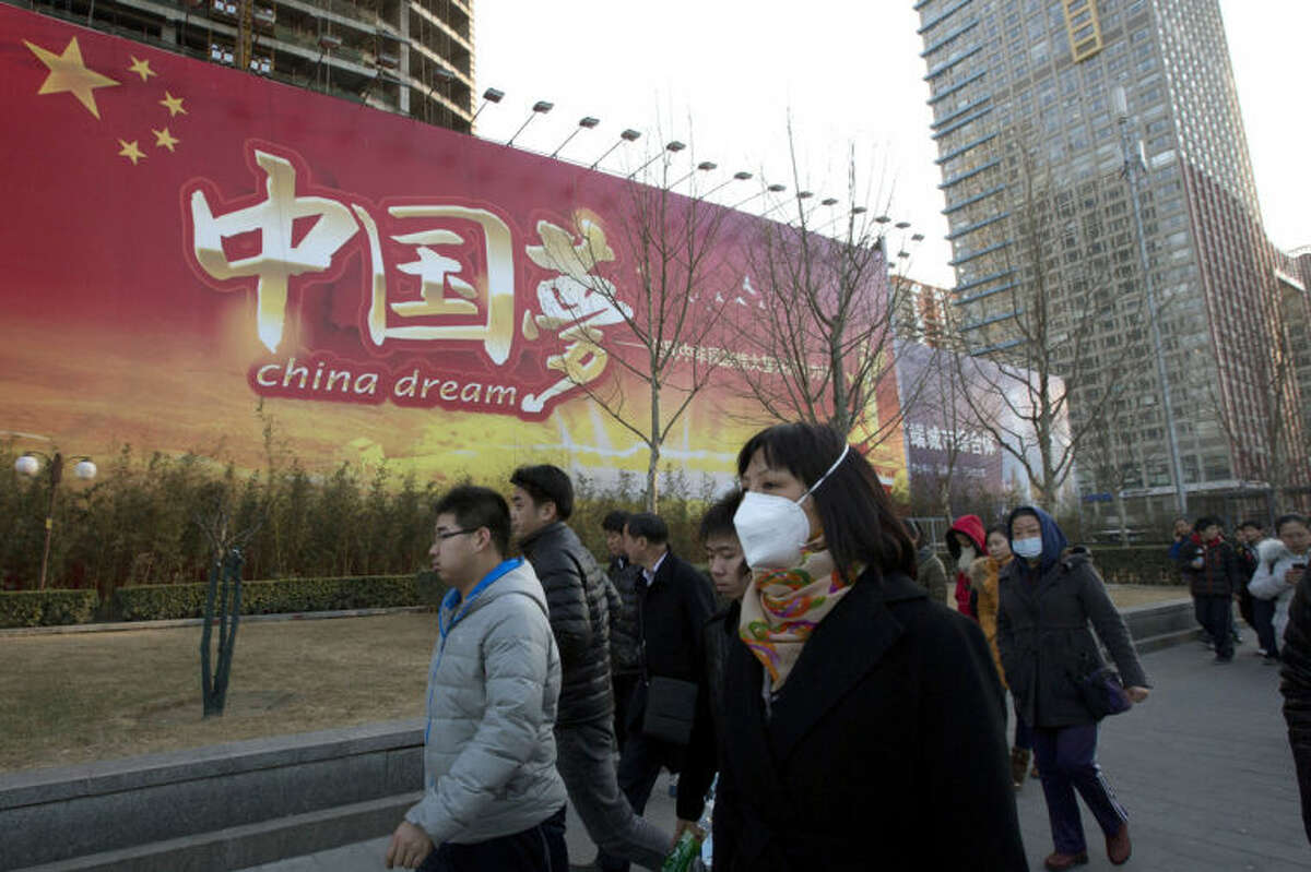 """Chinese women wearing masks walk past a Chinese government propaganda billboard with the words """"China Dream"""" in Beijing, China, Thursday, March 6, 2014. Combatting pollution has shot up the agenda of the ruling Communist Party, which for years pushed for rapid economic development with little concern about the environmental impact. Under public pressure to reduce the air pollution that blankets Beijing and cities across China, the country's leaders are rebalancing their priorities. (AP Photo/Ng Han Guan)"""