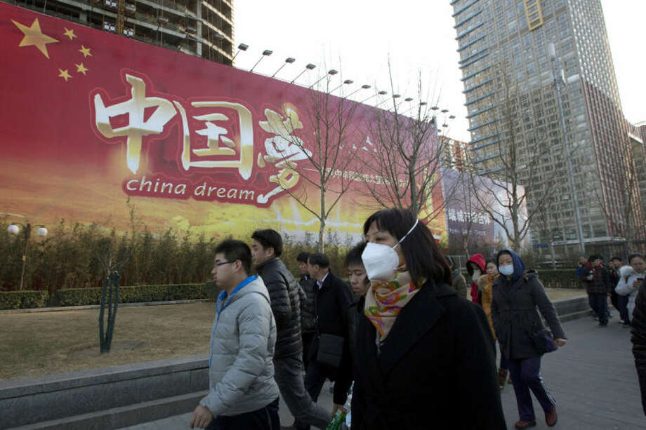 "Chinese women wearing masks walk past a Chinese government propaganda billboard with the words ""China Dream"" in Beijing, China, Thursday, March 6, 2014. Combatting pollution has shot up the agenda of the ruling Communist Party, which for years pushed for rapid economic development with little concern about the environmental impact. Under public pressure to reduce the air pollution that blankets Beijing and cities across China, the country's leaders are rebalancing their priorities. (AP Photo/Ng Han Guan)"