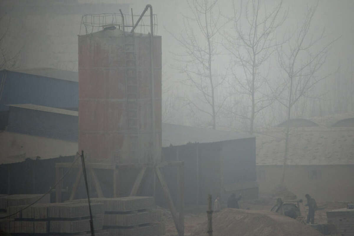 In this photo taken on Wednesday, Feb. 26, 2014, men work in a cement plant on a severely polluted day in Shijiazhuang, in northern China's Hebei province. Combatting pollution has shot up the agenda of the ruling Communist Party, which for years pushed for rapid economic development with little concern about the environmental impact. Under public pressure to reduce the air pollution that blankets Beijing and cities across China, the country's leaders are rebalancing their priorities.(AP Photo/Alexander F. Yuan)