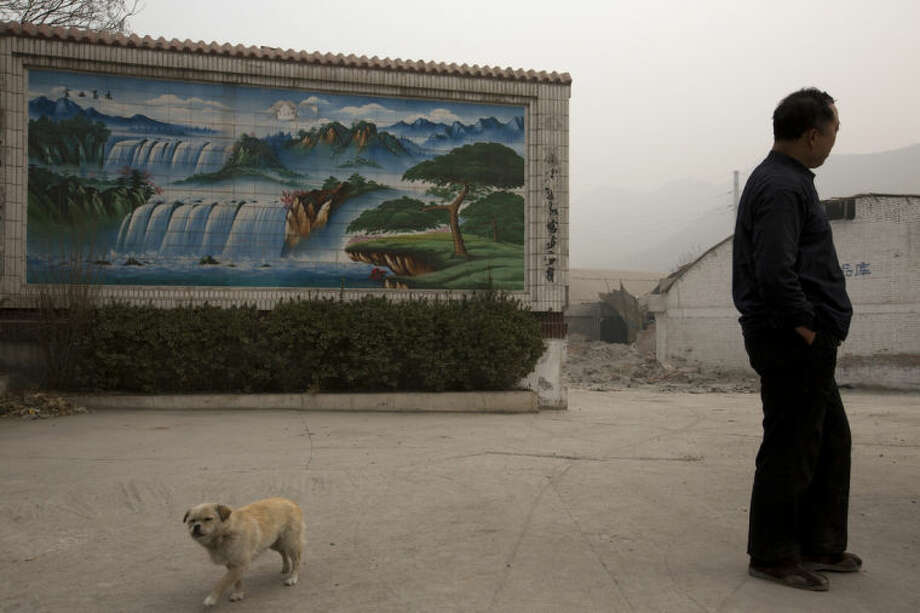 In this photo taken Wednesday, Feb. 26, 2014, a gatekeeper of a demolished cement plant and his dog stand near a mosaic scenic wall near the plant's gate on a severely polluted day in Shijiazhuang, in northern China's Hebei province. Combatting pollution has shot up the agenda of the ruling Communist Party, which for years pushed for rapid economic development with little concern about the environmental impact. Under public pressure to reduce the air pollution that blankets Beijing and cities across China, the country's leaders are rebalancing their priorities. (AP Photo/Alexander F. Yuan)