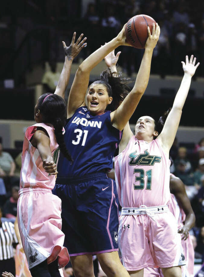 AP photoUConn senior center Stefanie Dolson (center) grabs a rebound away from a pair of South Florida players during a February game. Dolson has been named the American Athletic Conference Defensive Player of the Year and earned a berth on the all-conference first team. She is one of seven members of the unbeaten Huskies to earn conference recognition.