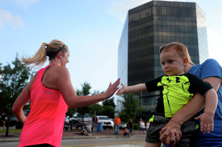 Kolin Frioux, 2, high fives a runner near the finish line during the Calder Twilight 5k on Friday evening. The event took runners and walkers down Calder Avenue and through the historic Old Town neighborhood.  Photo taken Friday 6/10/16 Ryan Pelham/The Enterprise Photo: Ryan Pelham / ©2016 The Beaumont Enterprise/Ryan Pelham