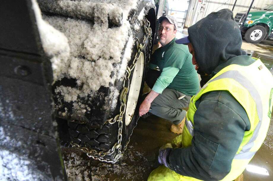 Hour Photo/Alex von Kleydorff Scott Phelan, an operator with Norwalk DPW and Neil Dennehy get a set of chains on Scott's plow truck as snow falls steadily on Thursday. Conditions worsened during the afternoon, he found that he was skidding so into the garage for chains