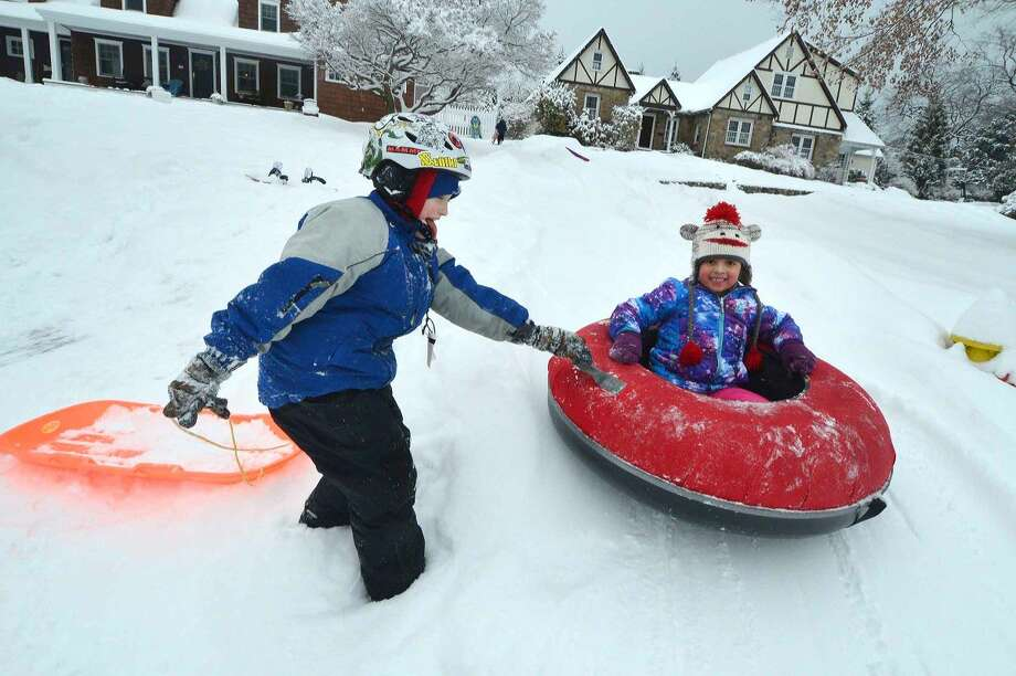 Hour Photo/Alex von Kleydorff A snow day finds 6yr old Camila Fernadez getting a push in her tube from 9yr old Raleigh Fiore while sledding down the hill in front of their houses