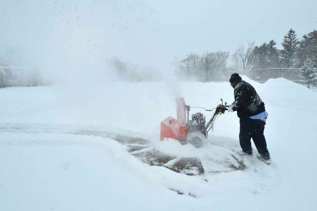 Hour Photo/Alex von Kleydorff Nathan Hale Middle School Head Custodian Stanley Shular turns the corner with a snowblower as the custodial staff clears snow on Thursday when school in Norwalk had been cancelled