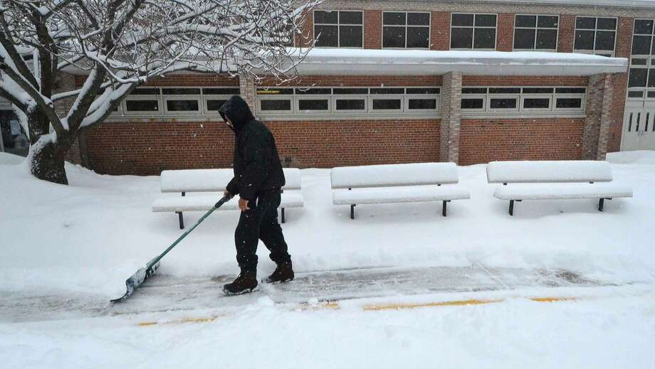 Hour Photo/Alex von Kleydorff No school for students in Norwalk but the custodial staff at Nathan Hale Middle school need to clear snow for Friday. Danny Thorne shovels one of the pathways near the entrance