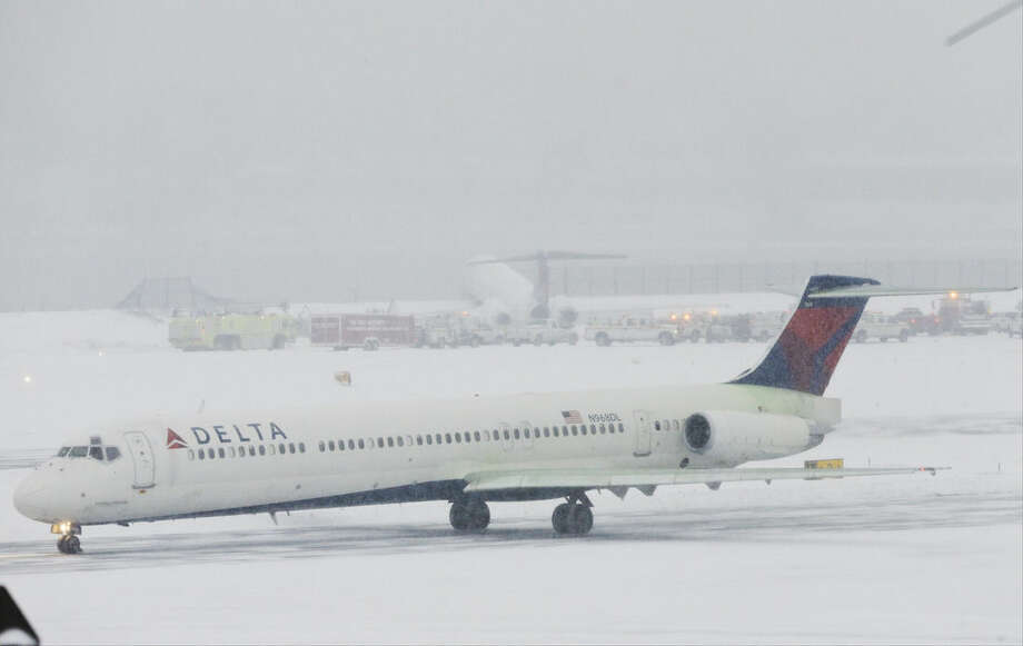A Delta plane passes Delta Flight 1086 that rests on a berm near the water at LaGuardia Airport, Thursday, March 5, 2015, in New York. The plane, from Atlanta, skidded off the runway while landing, and crashed through a chain-link fence. (AP Photo/Frank Franklin II) (AP Photo/Frank Franklin II)