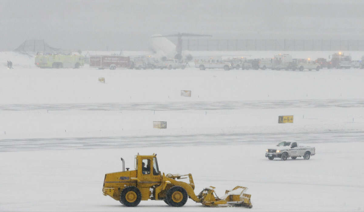 Grounds crews work to clear the runway near a Delta plane that rests on a berm near the water at LaGuardia Airport, Thursday, March 5, 2015, in New York. The plane, from Atlanta, skidded off the runway while landing, and crashed through a chain-link fence. (AP Photo/Frank Franklin II)