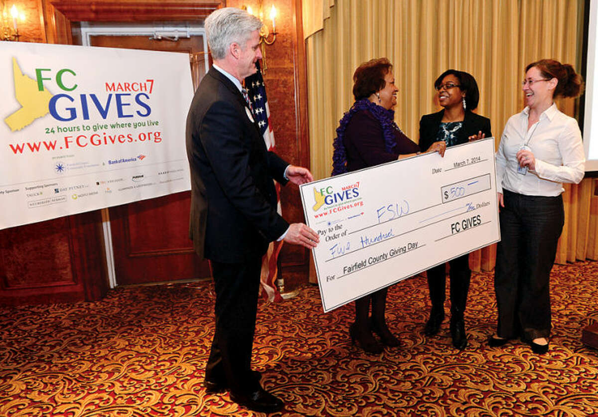 Hour photo / Erik Trautmann Bank of America Fairfield County Market President, Bill Tommins, Fairfield County Community Foundation, Juanita James, award a check for $500 to Allison Ousley and Katie Hill of FSW for their fundraising efforts 100 during the launch of Fairfield County Giving Day at the Norwalk Inn Friday morning. Fairfield County Giving Day is an initiative to raise $1 million for up to 400 Fairfield County, Connecticut nonprofits in 24-hours.