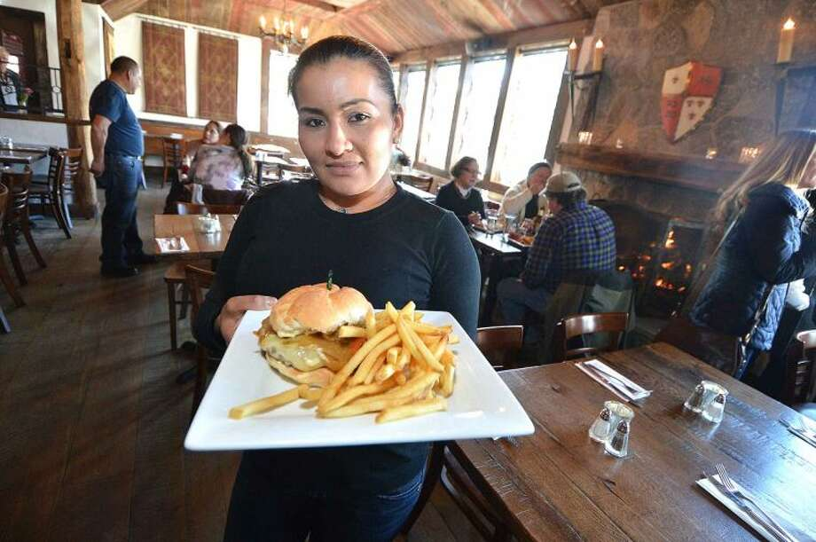 Server Marina Bonilla heads to the dining room with a cajun stout burger with smoked bacon and tabasco at The Little Pub on Danbury Road, just one of the many Restaurant Week options in the Wilton area.