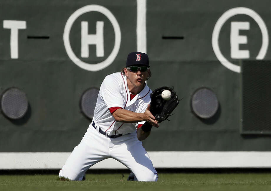 Boston Red Sox left fielder Blake Tekotte goes to his knees to grab a fly out by Miami Marlins' Austin Nola in the seventh inning of a interleague spring training baseball game in Fort Myers Fla., Friday March 6, 2015. (AP Photo/Tony Gutierrez)