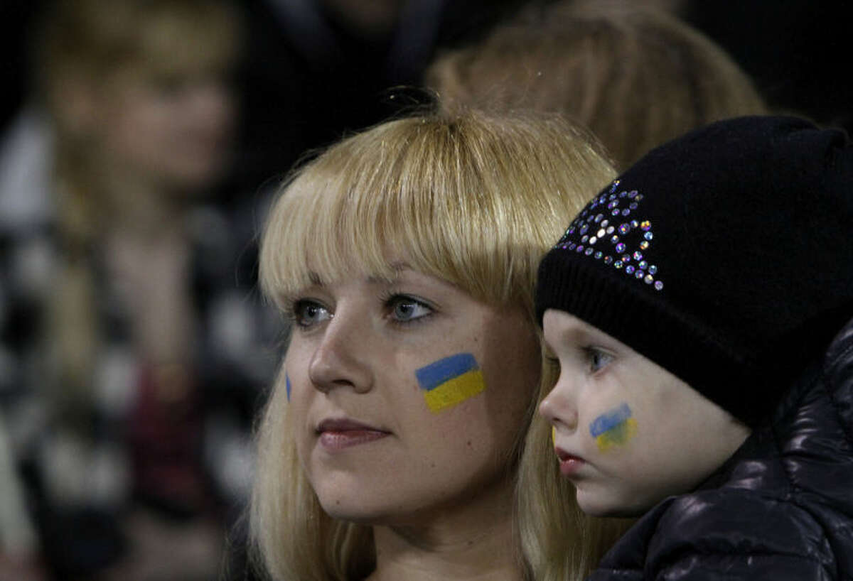 An Ukrainian woman with her baby, both with faces painted with the Ukrainian flag, watch their team during an international friendly match between Ukraine and U.S. at Antonis Papadopoulos stadium in southern city of Larnaca, Cyprus, Wednesday, March 5, 2014. The Ukrainians are to face the United States in a friendly on Wednesday in Cyprus, a match moved from Kharkiv to Larnaca for security reasons. (AP Photo/Petros Karadjias)
