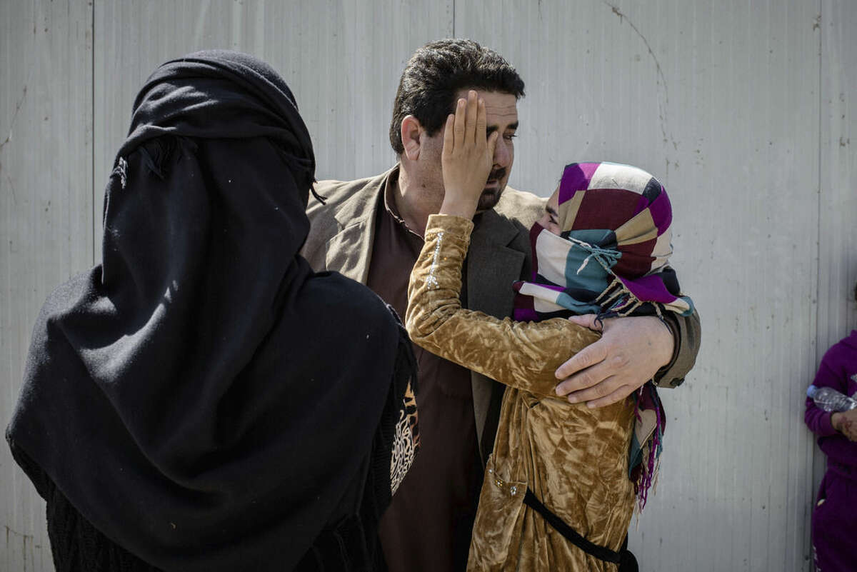In this Thursday, March 31, 2016 photo, Yumana, 13, wipes tears from the face of her father, Sheikh Matar, after being separated from him for over a year. Yumana was stuck with her mother, younger sister, and two younger brothers in Islamic State group controlled territory after her father was forced to flee to Kurdistan. They were able to come together when recent fighting between Iraqi forces and the IS created an opportunity for them to escape late the previous night. (AP Photo/Cengiz Yar)