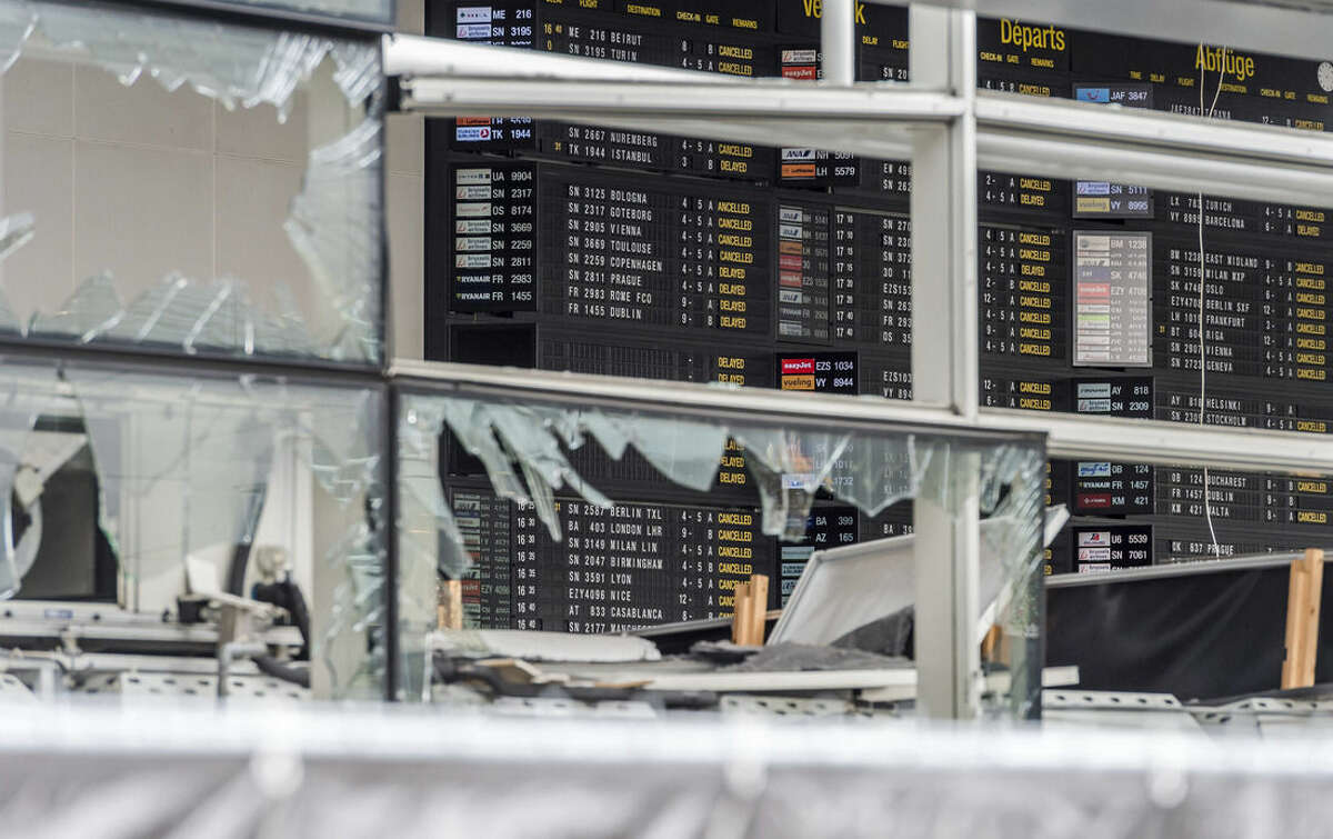 FILE - In this March 23, 2016 file photo, an arrivals and departure board is seen behind blown out windows at Zaventem Airport in Brussels. It's unclear when the Brussels Airport will reopen, even after a meeting Friday, April 1 by Prime Minister Charles Michel and key members of the government. (AP Photo/Geert Vanden Wijngaert, Pool)