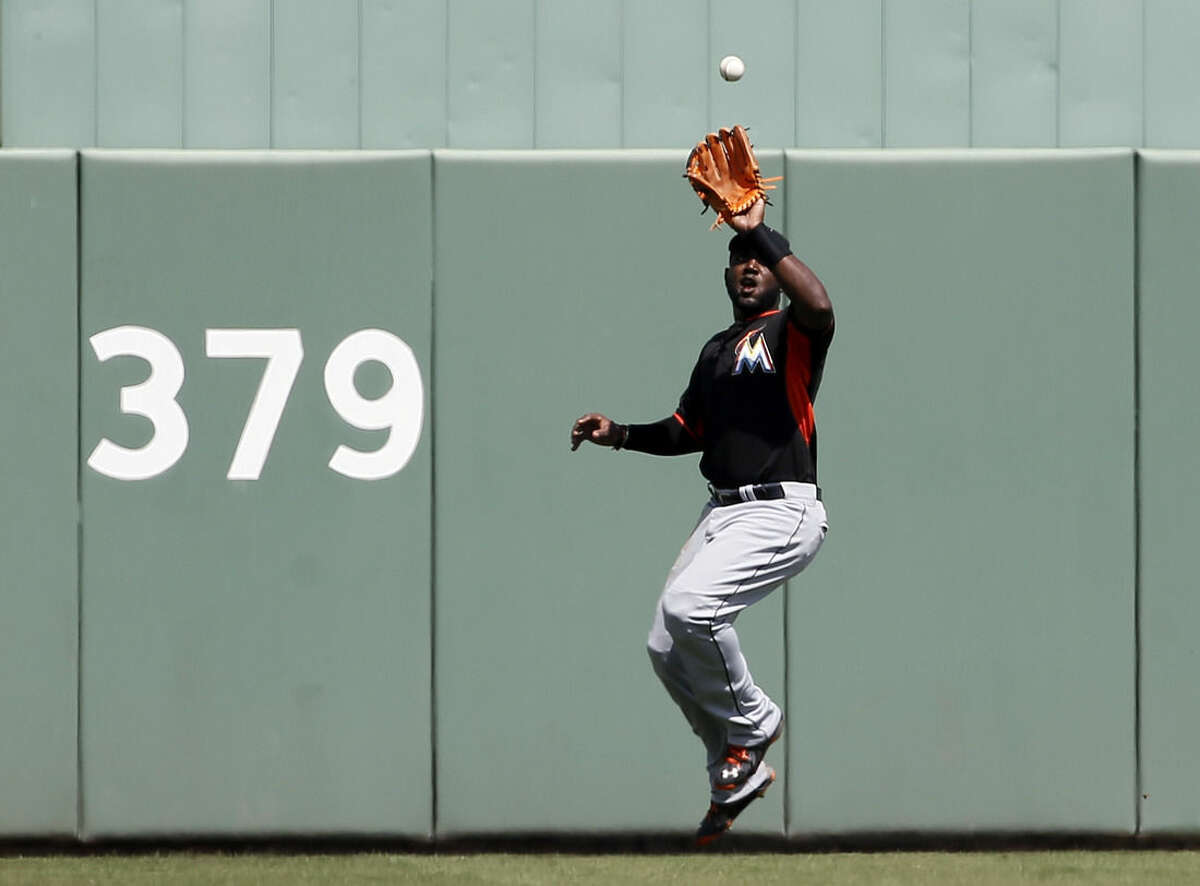 Miami Marlins' Marcell Ozuna reaches up to grab a Boston Red Sox's David Ortiz fly out in the first inning of an interleague spring training baseball game in Fort Myers Fla., Friday, March 6, 2015. (AP Photo/Tony Gutierrez)