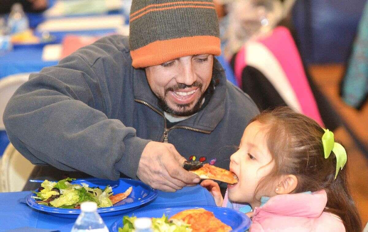 Hour Photo/Alex von Kleydorff 1st grader Alondra Sanchez and dad Raul enjoy pizza during the Literacy 4 Parents 4 Their Children program at Brookside School