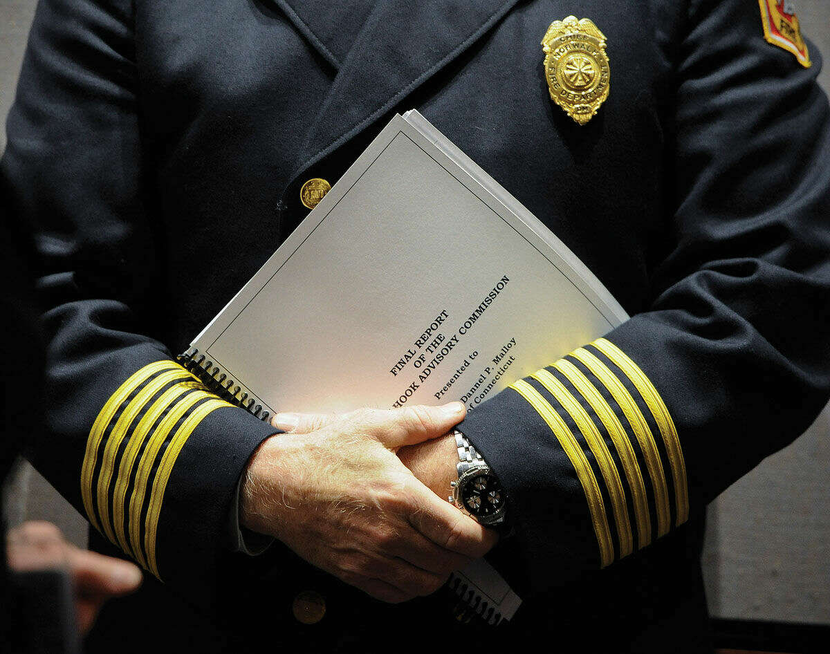 Commission member and city of Norwalk Fire Chief Denis McCarthy holds a copy of the final report from the Sandy Hook Advisory Commission after a presentation at the Legislative Office Building, Friday, March 6, 2015, in Hartford, Conn. The commission was formed to provide a review current policy and make recommendations in the areas of public safety, mental health, and gun violence prevention after the 2012 killings of 20 first-graders and six adults at Sandy Hook Elementary School. (AP Photo/Jessica Hill)