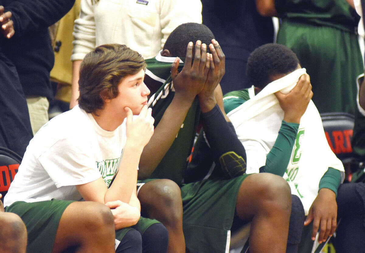 Hour photo/John Nash - Members of the Norwalk High boys basketball team react at the end of their FCIAC championship game loss to Westhill on Friday in Fairfield.