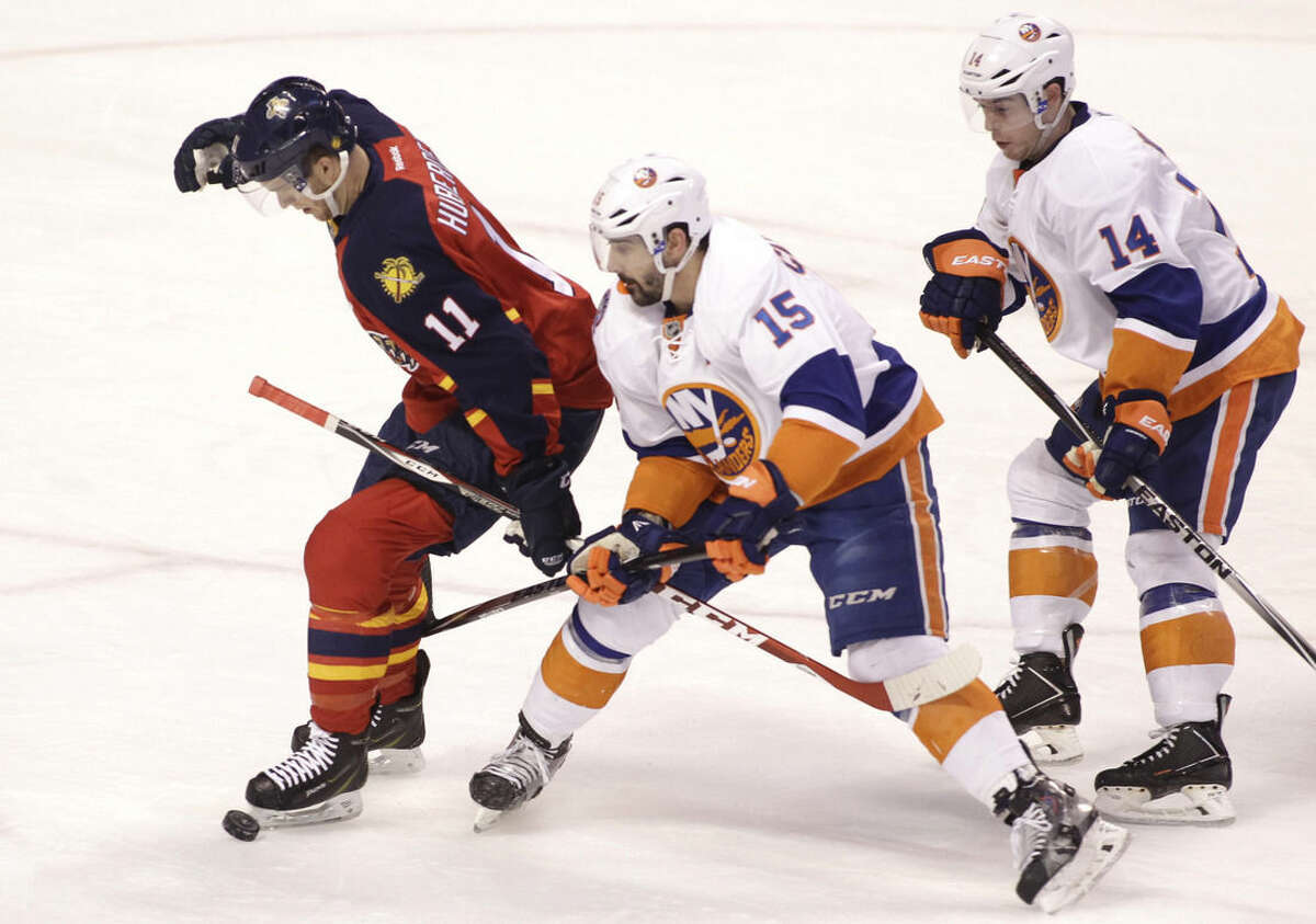 Florida Panthers' Jonathan Huberdeau (11) looks for the puck as New York Islanders' Cal Clutterbuck (15) and Thomas Hickey defend during the first period of an NHL hockey game, Saturday, March 7, 2015, in Sunrise, Fla. (AP Photo/Luis M. Alvarez)